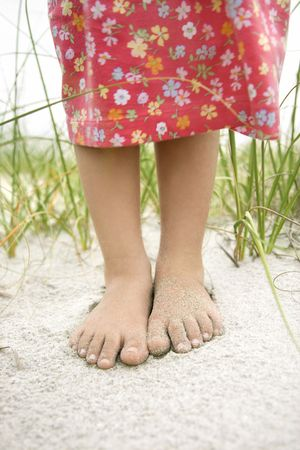 Closeup of a little girls barefoot feet that are covered in sand. Vertical shot. photo