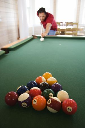 outside shooting: Racked pool balls as a man prepares to break. Vertical shot.