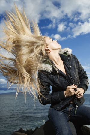 Attractive young woman sitting on a rock at the beach and flipping her long blond hair with the ocean in the background. Vertical shot. photo