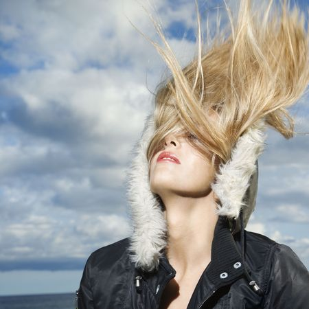 Attractive young woman is wearing a parka at the beach and flipping her long blond hair back. Square format. photo