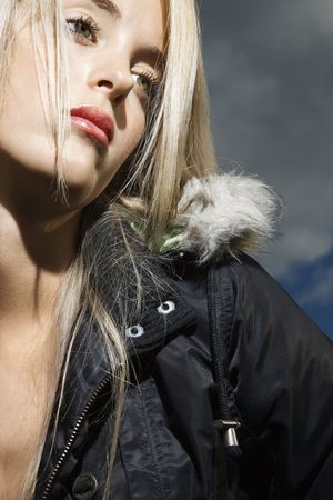 Attractive young woman wears a parka with an alluring look. Vertical shot. photo