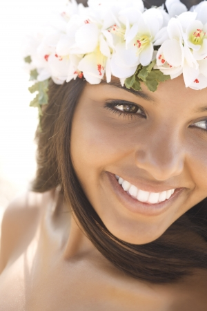 Attractive young Hawaiian woman with a lei on her head smiling. Vertical shot. photo