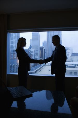 dandose la mano: Silueta de un empresario y empresaria agitando las manos. La ciudad puede verse a trav�s de la ventana en segundo plano. Un disparo vertical.  Foto de archivo