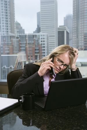 Caucasian businesswoman on the phone at her desk, holding her head and looking at a laptop computer with a frustrated expression. City buildings can be seen in the background through the window. Vertical shot. photo