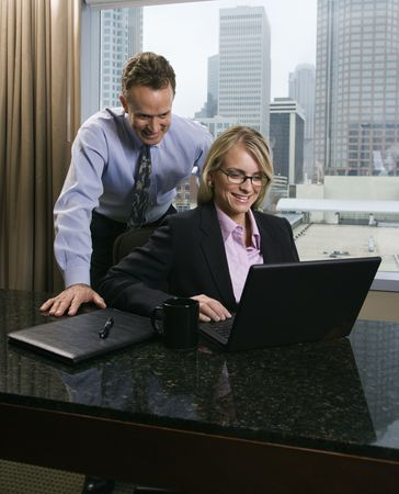 Caucasian businesswoman and middle-aged businessman smile as they look over a laptop computer. The city can be seen through the window in the background. Vertical shot. Stock Photo - 6455260