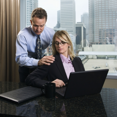 inappropriate: Caucasian businessman puts his hands on a businesswomans shoulders as she gives an annoyed look. They are in the office and the city can be seen in the background. Square shot.