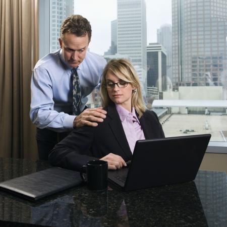 acoso laboral: Empresario del C�ucaso pone sus manos sobre los hombros de una empresaria como ella da una mirada molesta. Est�n en la Oficina y la ciudad puede verse en el fondo. Disparo cuadrados.
