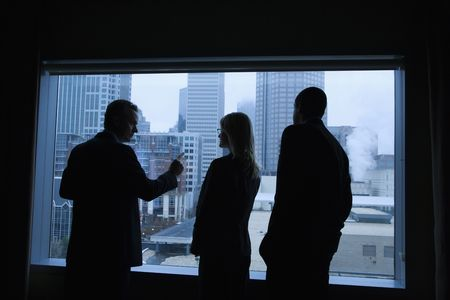 one to one meeting: Businesspeople silhouetted in front of a large window that overlooks the city. Horizontal shot.
