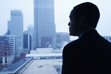 daydream: African-American businessman looking out of a window at the city. Horizontal shot. Stock Photo
