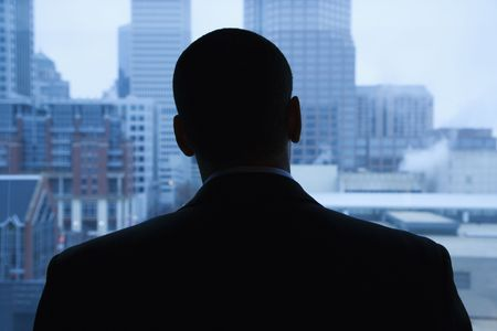 Rear view of an African-American businessman looking out of a window at the city in the distance. Horizontal shot.