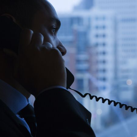 Side view of an African-American businessman speaking over the telephone. A window with a city view is in the background. Square shot. Stock Photo - 6420905