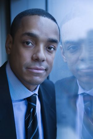 African-American businessman smiles towards the camera. His reflection can be seen in the window. Vertical shot. Stock Photo - 6455251