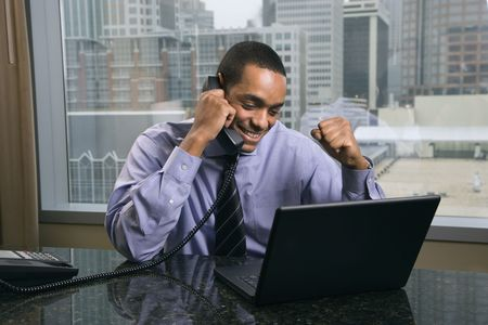 excited people: African-American businessman raises his arm in excitement while talking on the phone. He is looking at a laptop on his desk. Horizontal shot.