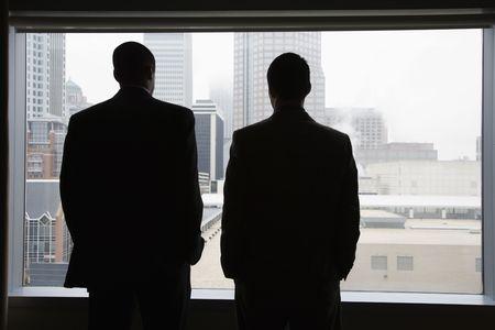 En la parte posterior vista de dos empresarios como que mirar por una gran ventana con una vista de la ciudad. Tienen en sus manos en sus bolsillos. Vista horizontal. Foto de archivo