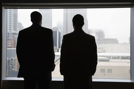 back to camera: Rear view of two businessmen as they stare out a large window with a city view. They have their hands in their pockets. Horizontal view.