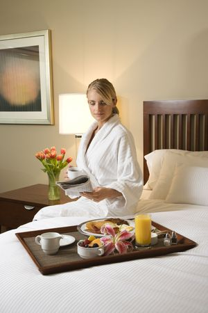 Caucasian woman wearing a bathrobe sits on a hotel bed with tray of breakfast. She is reading a newspaper and holding a coffee cup. Vertical format. Stock Photo - 6455192
