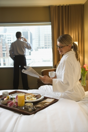 breakfast hotel: Caucasian woman in a robe sits on a hotel bed while reading the newspaper. A man stands in the background talking on his mobile phone. Vertical shot.
