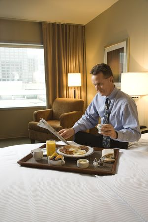 Caucasian businessman enjoys his breakfast while reading the morning paper. He is sitting on the bed and holding a cup of coffee. Vertical shot. photo