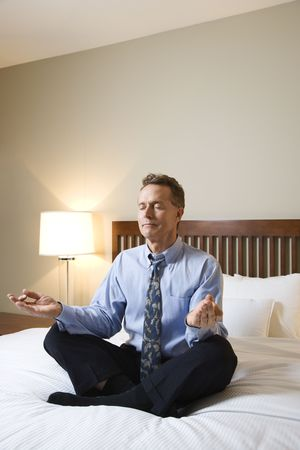 Caucasian businessman sits on a bed in the lotus position while meditating with closed eyes. Vertical shot. Stock Photo - 6455185