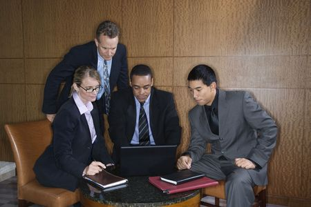 ethnically diverse: Ethnically diverse group of businessmen and a businesswoman look at a laptop computer screen. Horizontal shot. Stock Photo