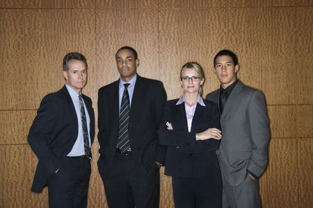 ethnically diverse: Ethnically diverse businessmen and a businesswoman stand in a lineup as they look towards the camera. Horizontal shot.