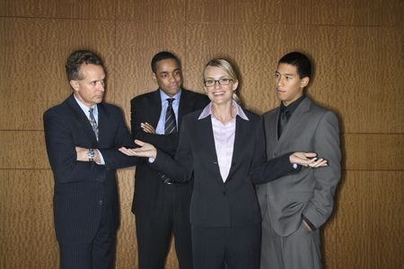 Caucasian businesswoman stands smiling with her hands out as businessmen look at her disapprovingly. Horizontal shot. photo