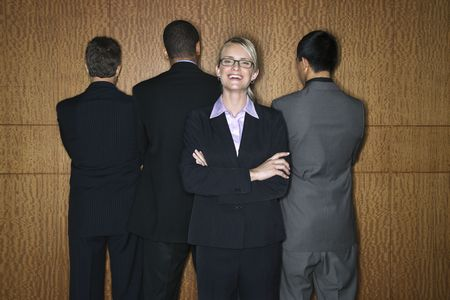 sexes: Caucasian businesswoman stands smiling as businessmen stand with their backs turned. Horizontal shot.