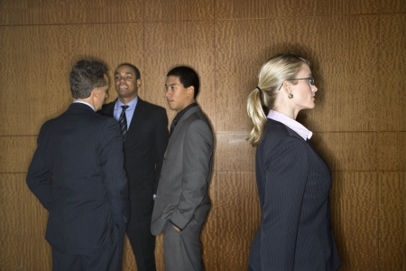 Businessmen of ethnic diversity talk in a group as a Caucasian businesswoman walks by. Horizontal shot.