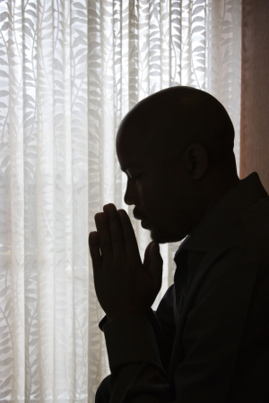 Profile of African-American man silhouetted by a window with his head bowed and his hands in prayer. Vertical shot.
