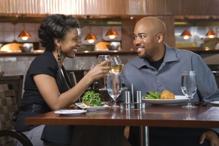 up date: African-American couple dining out. They are toasting with glasses of white wine and smiling. Horizontal shot. Stock Photo