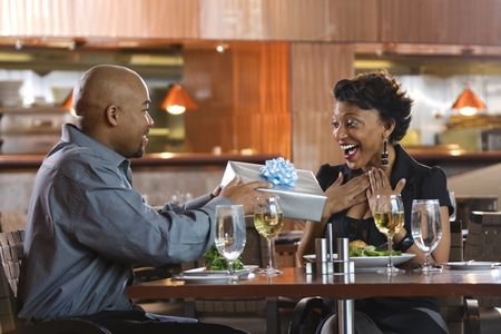 African-American man giving a surprised woman a gift-wrapped present at a restaurant. Horizontal shot. photo