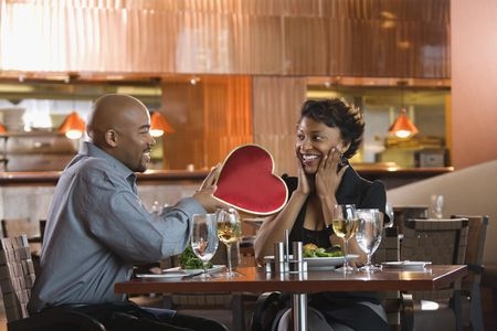 African-American gives a Valentine Day heart box to a surprised woman at a restaurant. Horizontal shot. photo