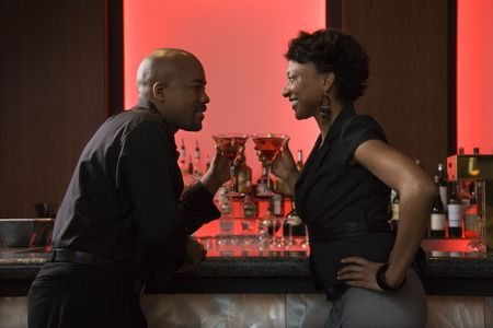 adult dating: African-American man and woman face each other at a bar while enjoying martinis. Horizontal shot. Stock Photo