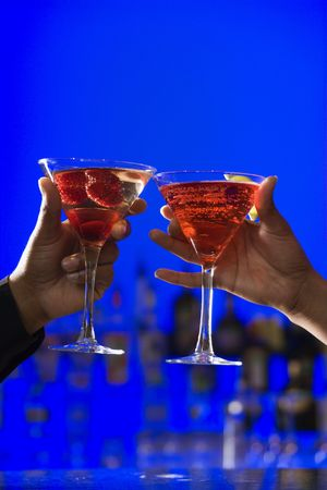 African-American hands toast martini glasses against a bright blue background. Vertical shot. photo