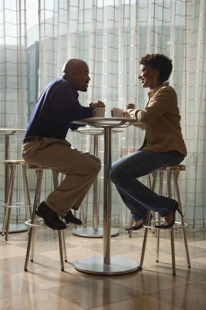 An African-American man and woman enjoy each others company over a cup of coffee.  They are seated at a small cafe table on stools. Vertical shot.