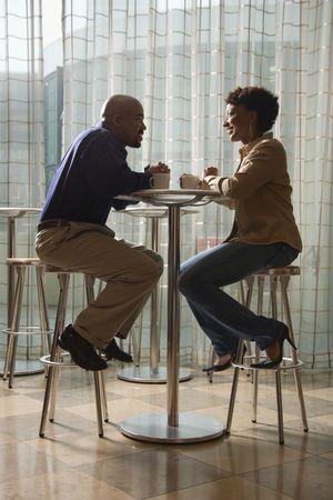 dos personas conversando: Un hombre afroamericano y una mujer disfrutan de la otra compa��a sobre una taza de caf�.  Ellos son sentados en una mesa de caf� peque�o en las heces. Un disparo vertical. Foto de archivo