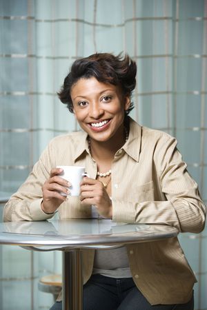 Attractive African-American woman sits at a table. She is holding a coffee cup and smiling towards the camera. Vertical shot. photo
