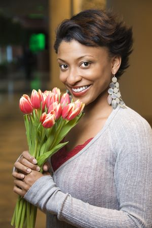 Attractive young African-American woman smiles for the camera. She is holding a bouquet of tulips. Vertical shot. photo