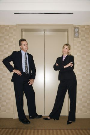 Caucasian businesswoman and businessman stand impatiently as they wait for an elevator. Vertical shot. photo