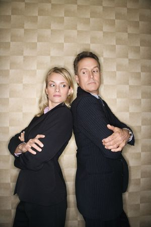 Caucasian mid-adult businesswoman and middle-aged businessman standing back to back and peering at each other over their shoulders. Vertical format. photo