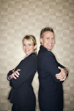 Caucasian mid-adult businesswoman and middle-aged businessman standing back to back and smiling at the camera. Vertical format. photo