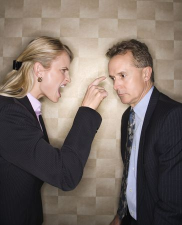 Caucasian mid-adult businesswoman yelling and pointing at middle-aged businessman. Vertical format. Stock Photo