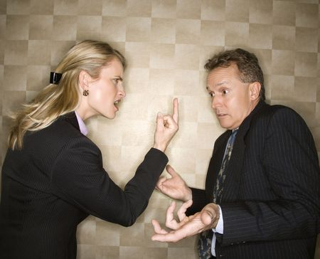 man scolding: Caucasian mid-adult businesswoman angrily giving middle finger to middle-aged businessman who shrugs at her. Horizontal format.
