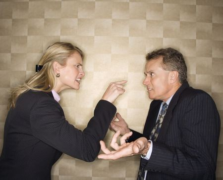 Caucasian mid-adult businesswoman yelling and pointing at middle-aged businessman, who shrugs at her. Horizontal format. photo