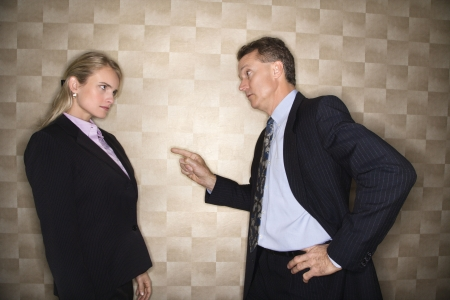 Caucasian middle-aged businessman pointing to and reprimanding mid-adult Caucasian businesswoman. Horizontal format. Stock Photo