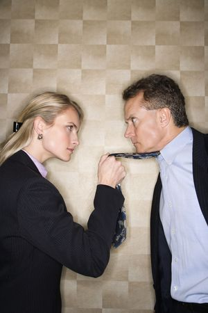 Caucasian mid-adult businesswoman staring into eyes of a middle-aged businessman while pulling angrily on his tie. Vertical format.
