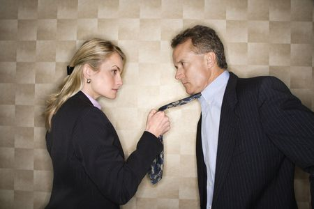 Caucasian mid-adult businesswoman staring into eyes of a middle-aged businessman while pulling on his tie. Horizontal format. photo
