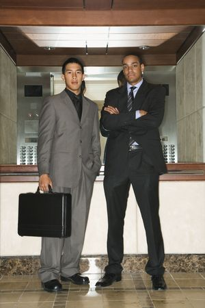 Young adult Asian and African-American businessmen standing in an office lobby looking at the camera. Vertical format. Stock Photo - 6455427