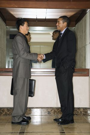 Young adult Asian and African-American businessmen standing in an office lobby shaking hands. photo