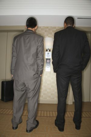Rear view of two young adult businessmen waiting for an elevator. Vertical format. photo